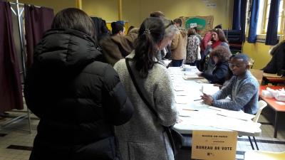 1. On entre dans le bureau de vote et on montre une preuve d'identité 2. On prend au moins deux bulletins de vote.